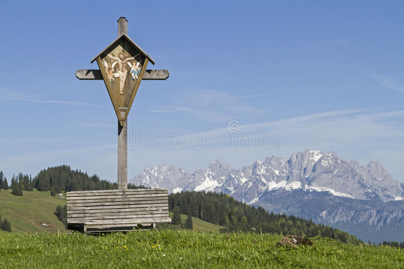 Wooden cross and Kaiser mountains stock images