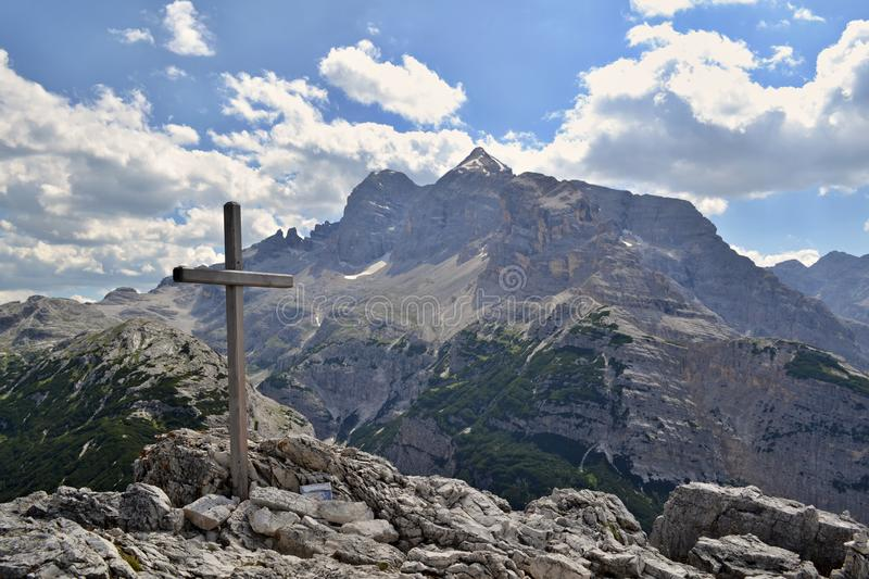 Wooden cross on a mountain peak with mountains under blue sky and white clouds in the background royalty free stock photos