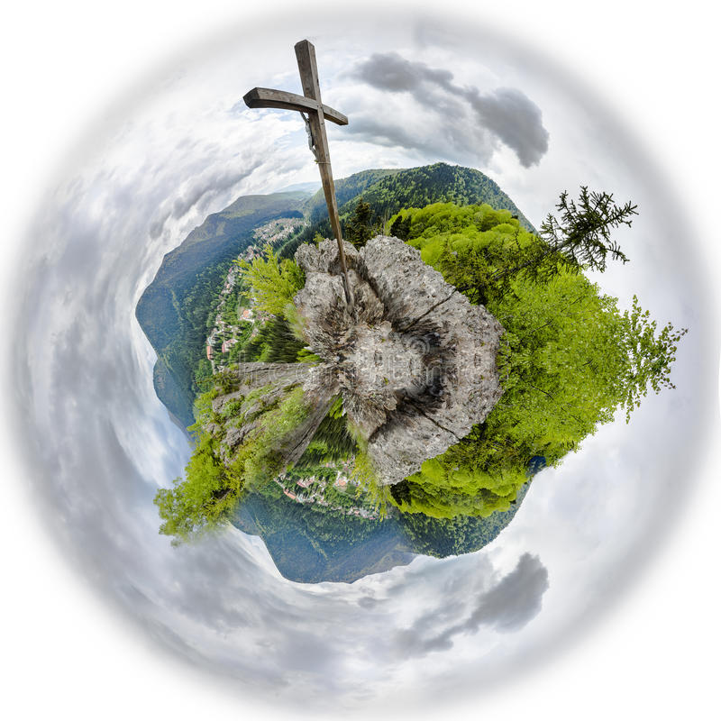 Wooden cross on mountain peak. Tiny planet stock photo
