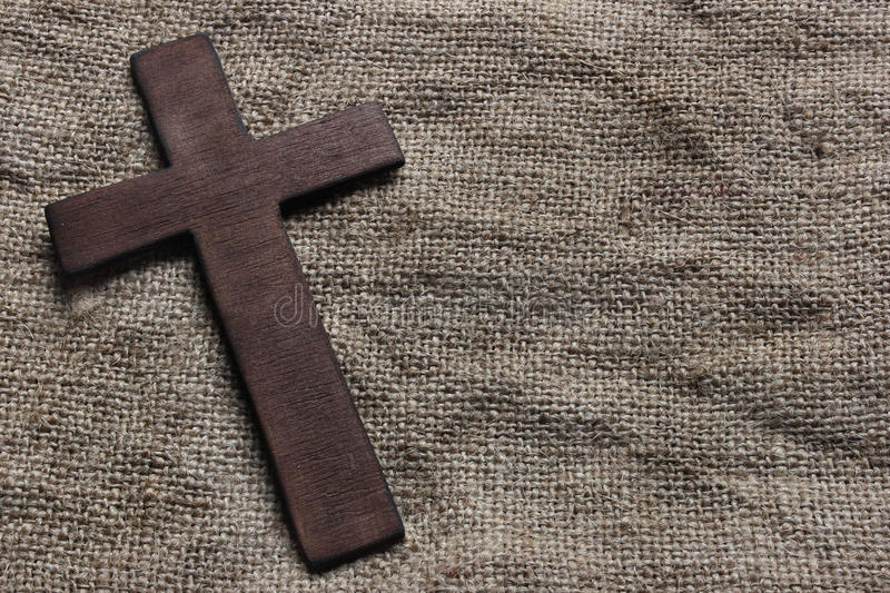 Wooden cross. On old canvas stock photography