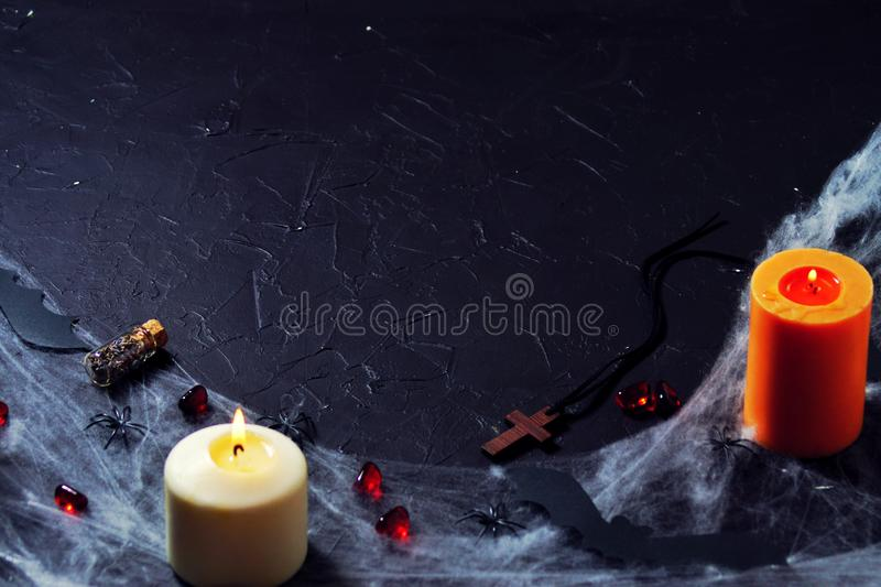 Halloween wooden cross lying next to a burning candle on a web with spiders and bats on a black background. vertical. Wooden cross, old runes, pentagram and stock photography