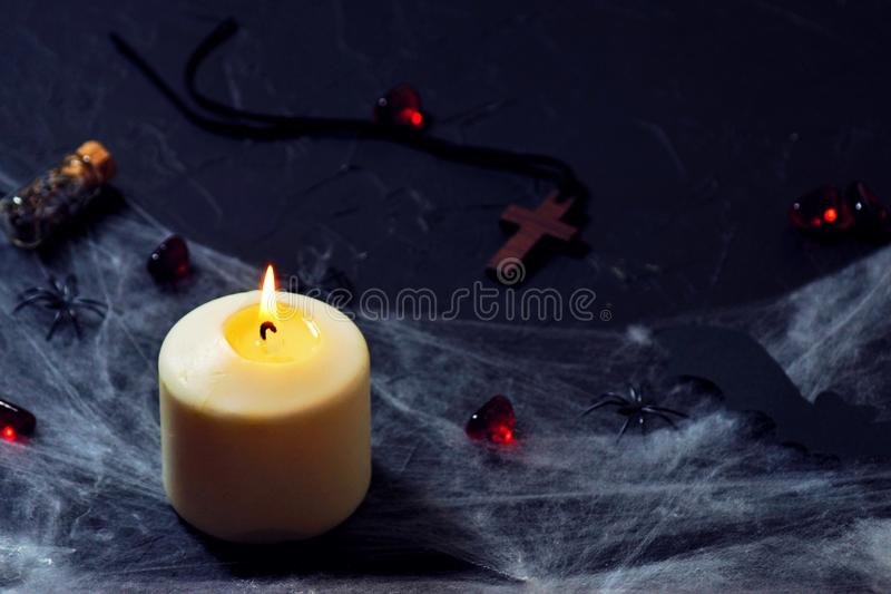 Halloween wooden cross lying next to a burning candle on a web with spiders and bats on a black background. horizontal. Wooden cross, old runes, pentagram and royalty free stock photography