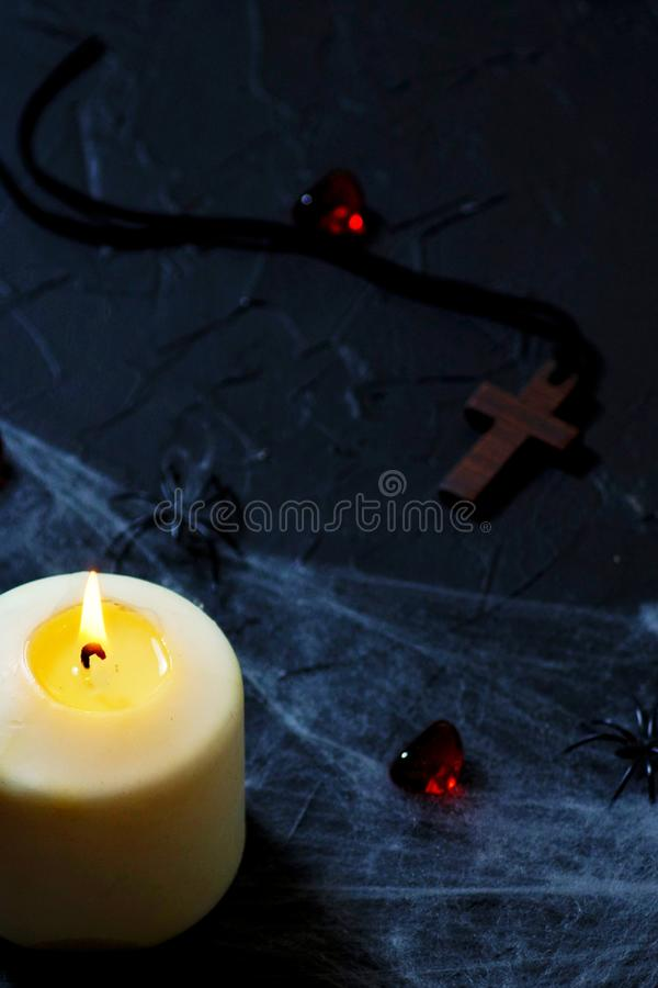Halloween wooden cross lying next to a burning candle on a web with spiders and bats on a black background. vertical stock photography