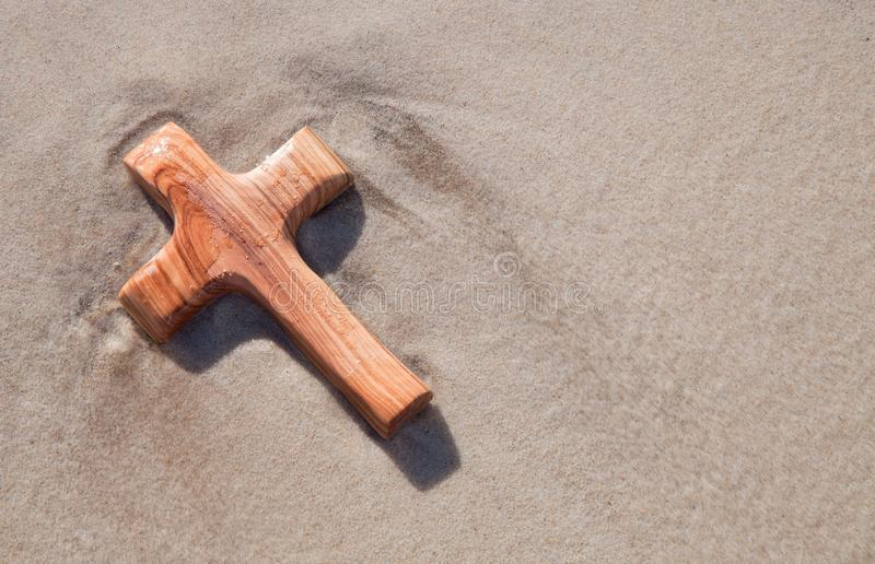 Wooden cross in sand - card for mourning royalty free stock images