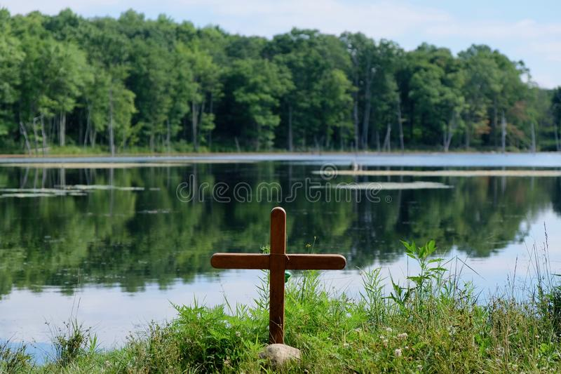 Wooden Cross on Shore of Lake stock images