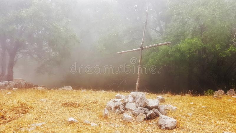 A wooden cross. Of simple build, on the grounds of Jabal Moussa natural reserve, Lebanon, symbol, christ, chrstian, christian, christianity, belief, myst, fog stock photography
