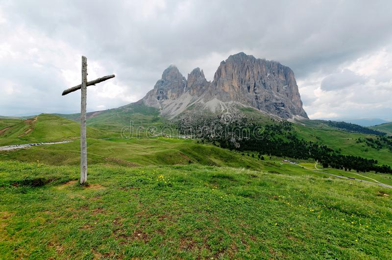 A wooden cross standing on the green grassy meadow at the foothills of rugged Langkofel-Plattkofel Mountains. Sassolungo-Sassopiatto on a sunny summer day, in royalty free stock photos