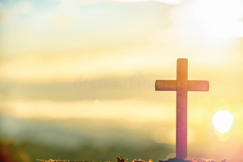 Wooden cross at sunrise in morning time with holy and light background .Crucifixion of jesus christ sign catholic religion concept. Wooden cross at sunrise in royalty free stock image