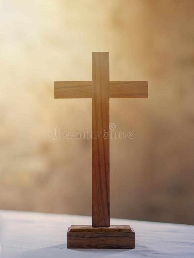 Wooden cross on white altar cloth, rays of light in background. Christian faith. stock photo