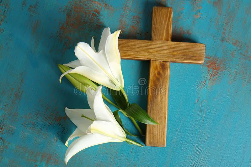 Wooden cross and white lily. On table stock image