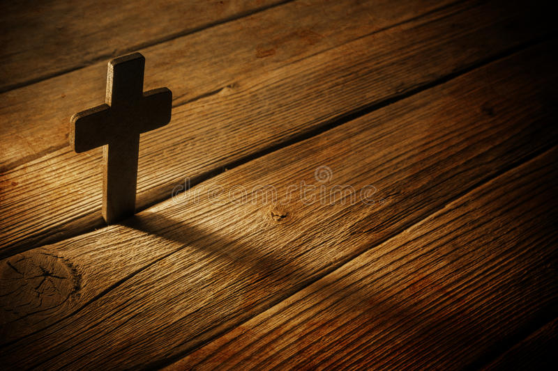 Wooden cross. On wood background royalty free stock photography