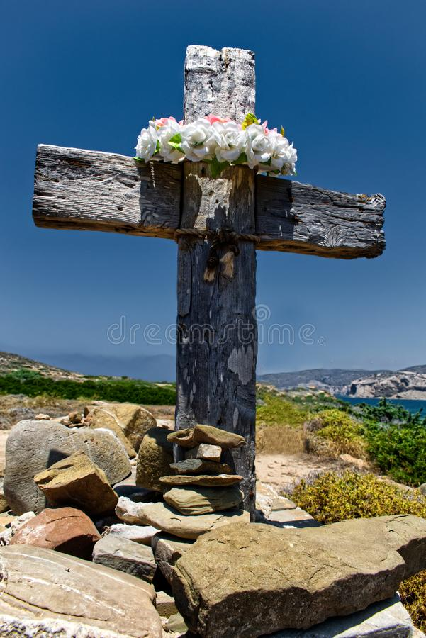 Wooden cross with wreath in background of landscape royalty free stock photo
