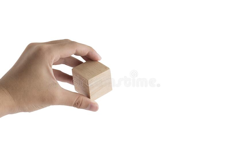 Wooden cube block grabbed by human hand stock images