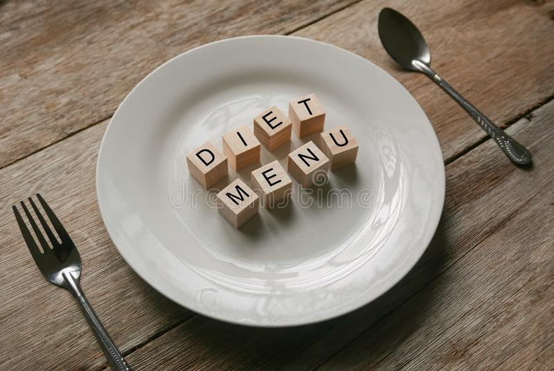 Wooden cube written with 'DIET MENU' on white plate with spoon and fork on wooden background. Food and diet concept. Meal, alphabet, breakfast stock images