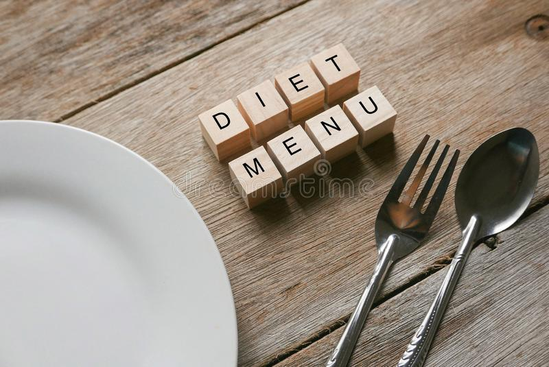 Wooden cube written with 'DIET MENU' on wooden background with white plate, spoon and fork . Food and diet concept. Meal, alphabet, breakfast royalty free stock photo