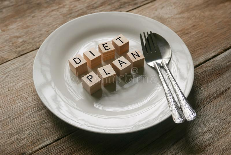Wooden cube written with 'DIET PLAN' on white plate with spoon and fork on wooden background. Food and diet concept royalty free stock image