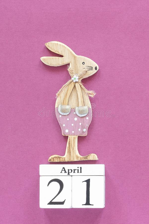 Wooden cubes calendar April 21 and easter bunny on purple paper background. Concept Catholic Easter Template for lettering, text royalty free stock photos