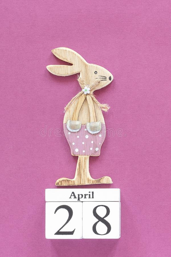 Wooden cubes calendar April 28 and wooden easter bunny on purple paper background. Concept Christian Easter Template for. Lettering, text or your design stock image