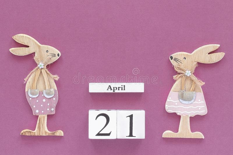 Wooden cubes calendar April 21 and pair of wooden easter bunnies on purple paper background. Concept Catholic Easter. Copy space Template for lettering, text or stock images