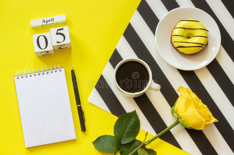 Wooden cubes calendar April 5th. Cup of coffee, yellow donut and rose on black and white napkin, empty open notepad for text on stock image