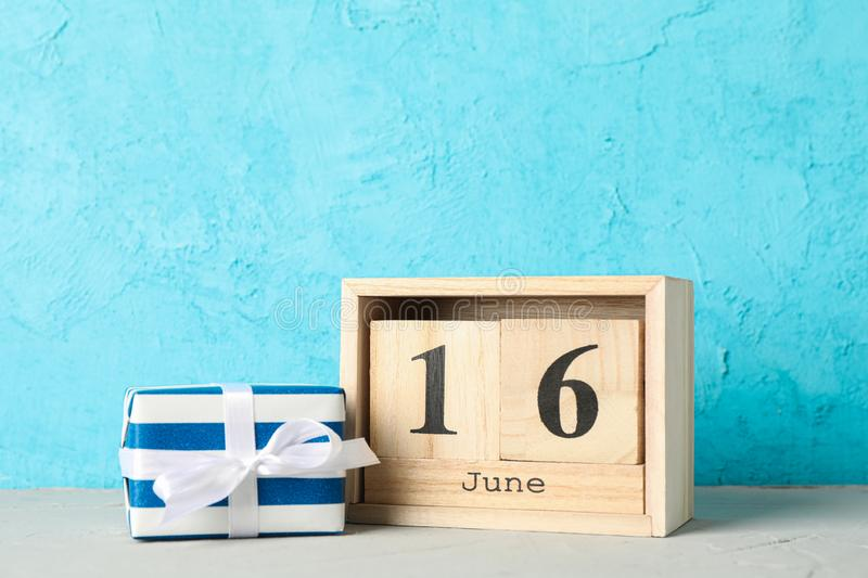 Wooden cubes calendar date June 16 and gift box on white table against color background. Space for text royalty free stock image