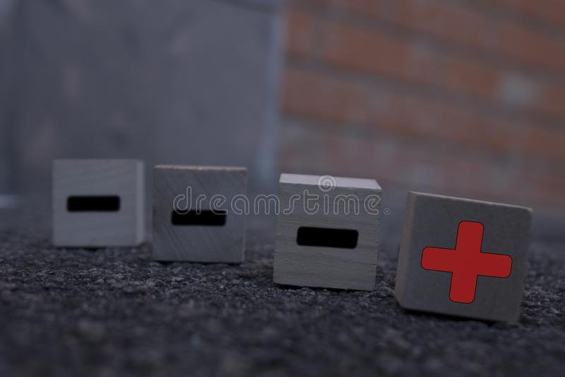 Wooden cubes with drawn plus and minus signs on the dark background, standing out from the crowd concept stock images