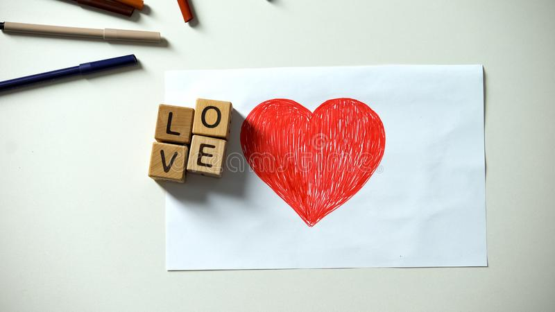 Wooden cubes with love word lying on red heart picture, true relationships. Stock photo royalty free stock images