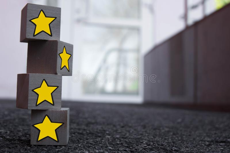 4 wooden cubes with a pattern of a yellow star standing on top of each other on asphalt stock photography