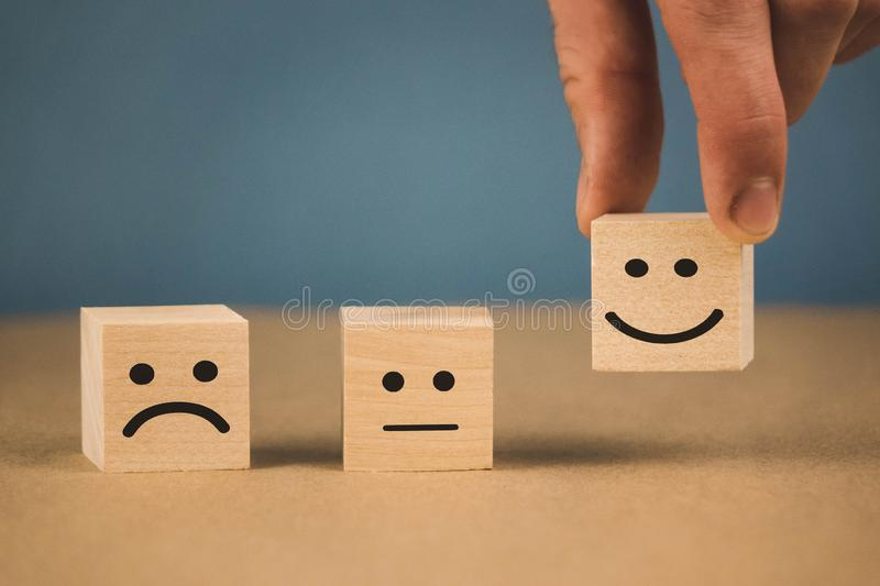 Wooden cubes with smiling emoticons and sad one. Business choice background design face technology cheerful customer emotion expression friendly happiness happy royalty free stock photography