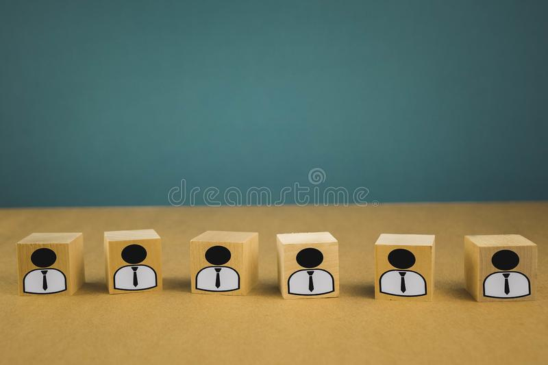wooden cubes standing in a row, meaning wage workers standing in one line, abstraction on a blue background stock photography