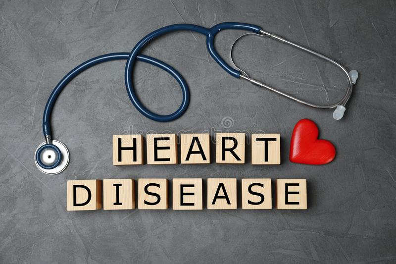 Wooden cubes with text Heart Disease and stethoscope on grey background. Flat lay stock photography