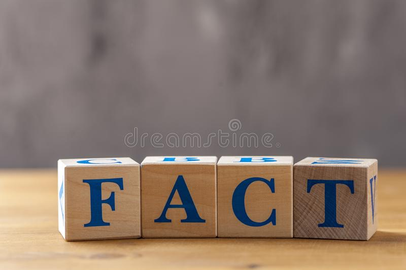 Wooden cubes with word FACT on table. Cubes with blue letters royalty free stock photo