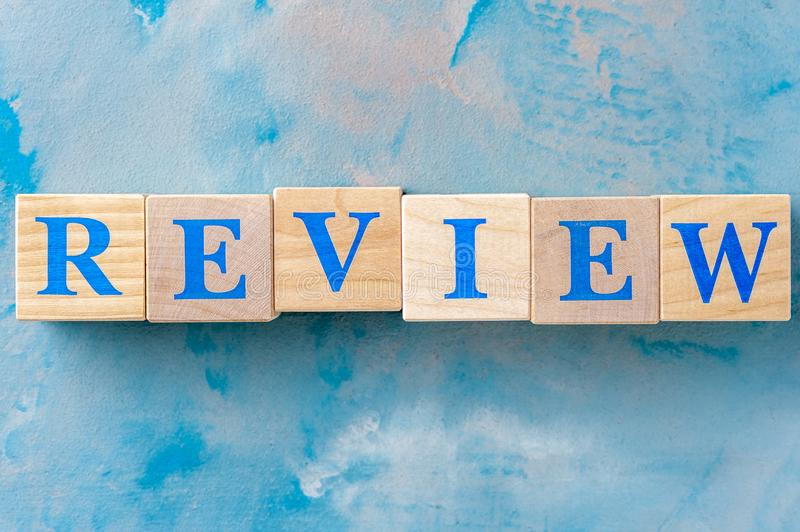 Wooden cubes with word REVIEW on blue table. Cubes with blue letters royalty free stock photos