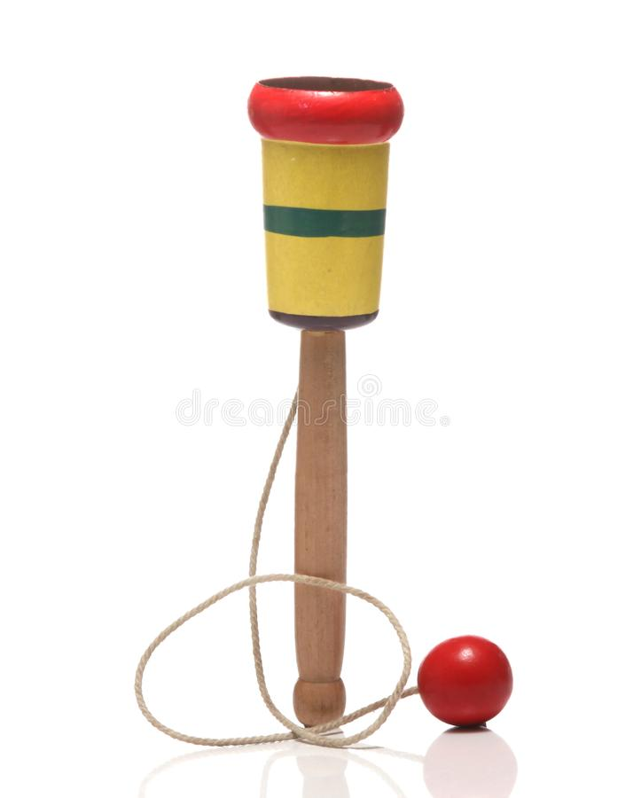 Wooden Cup-and-ball ball in cup toy. Wooden Cup-and-ball ball in cup toy close up on white background stock photo