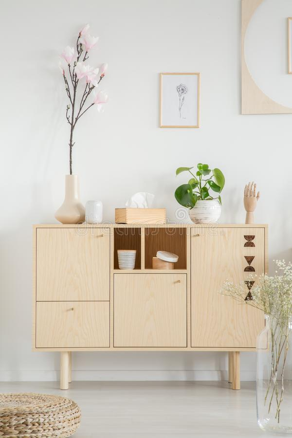 Wooden cupboard with flowers in white room interior with posters and pouf. Real photo royalty free stock photos