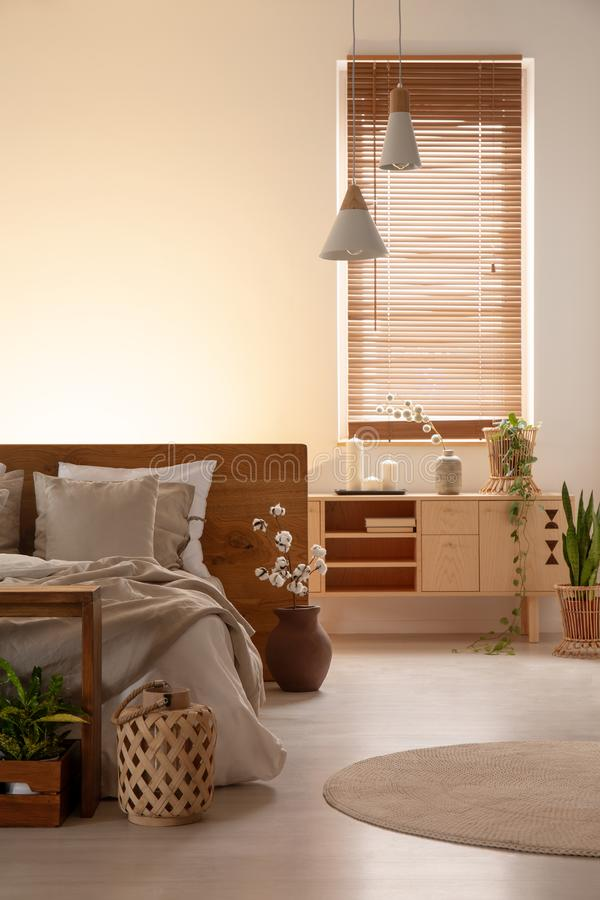 Wooden cupboard next to bed in bedroom interior with lamps and blinds on window. Real photo. Concept royalty free stock image