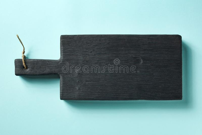 Wooden cutting board on blue background, from above royalty free stock photos