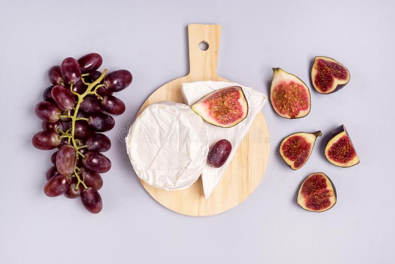 Wooden Cutting Board with Brie Cheese and Cutting Figs Ripe Grape and Figs Blue Background Top View Flat Lay Food or Snackfor Wine.  royalty free stock image