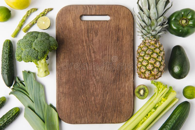Wooden cutting board with green vegetables and fruits isolated on white background stock images