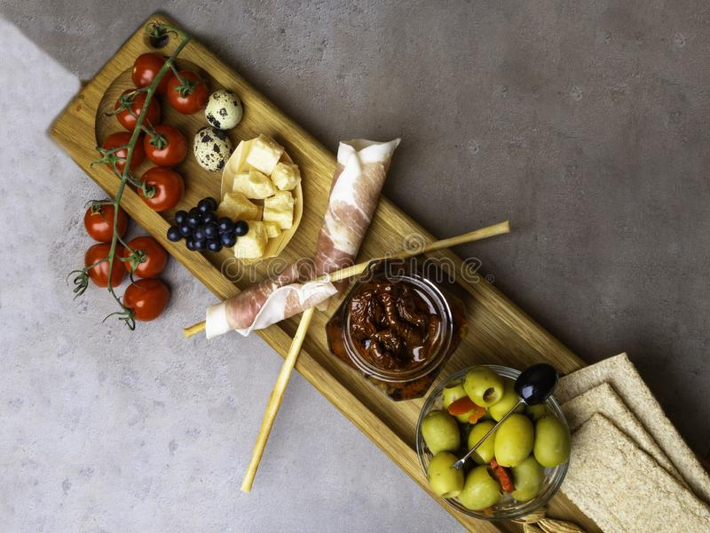 Wooden cutting board with Prosciutto Ham, red Dried and fresh tomatoes, Green Olives, bell pepper, Olives, parmesan cheese, nuts, royalty free stock photo