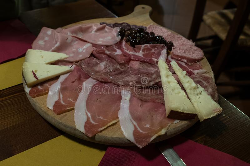 A wooden cutting board with typical Urbino gastronomic products. Cheeses and cold cuts stock photos