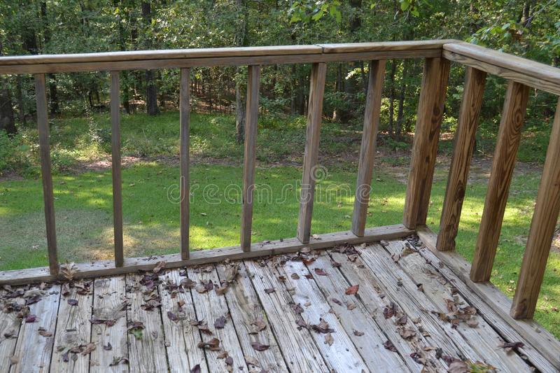 Wooden deck in backyard. Railing on grunge wooden plank deck covered in leaves in sunny backyard royalty free stock photo