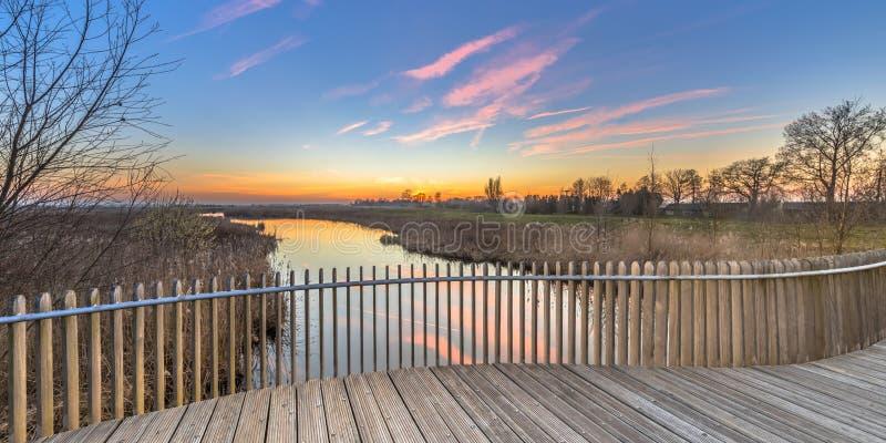 Wooden deck balustrade sunset over swamp. Bright sunset over Wooden deck balcony of bridge in Onlanden Nature reserve waterlogging area Groningen, Netherlands royalty free stock photography