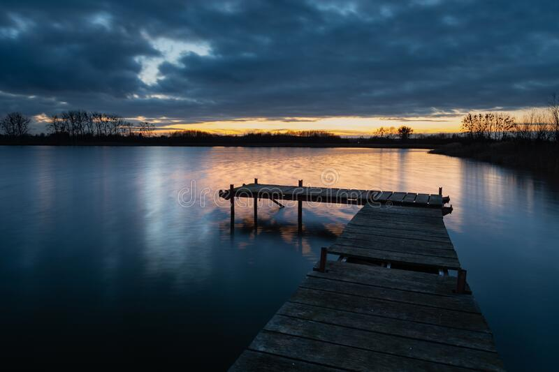 Wooden deck bridge and evening clouds after sunset over the water, view in december day stock image