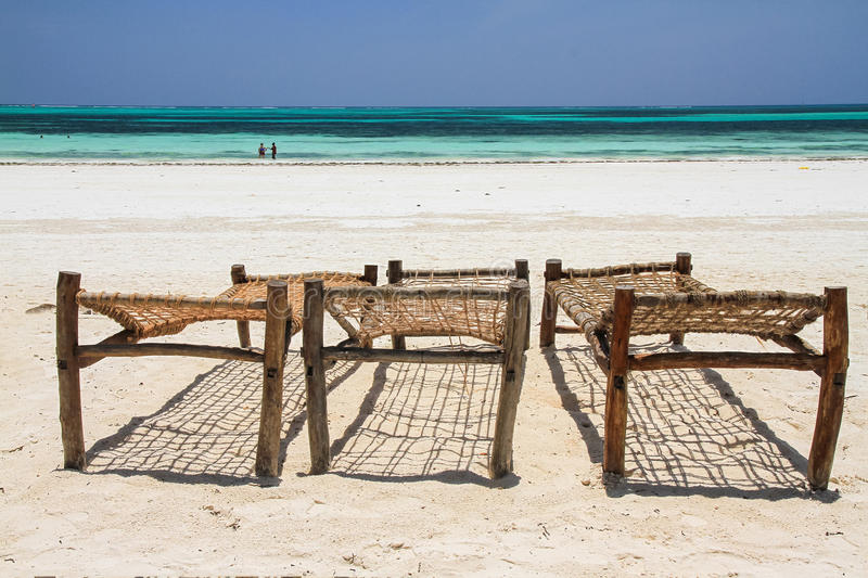 Wooden deck chairs on the beach royalty free stock photo
