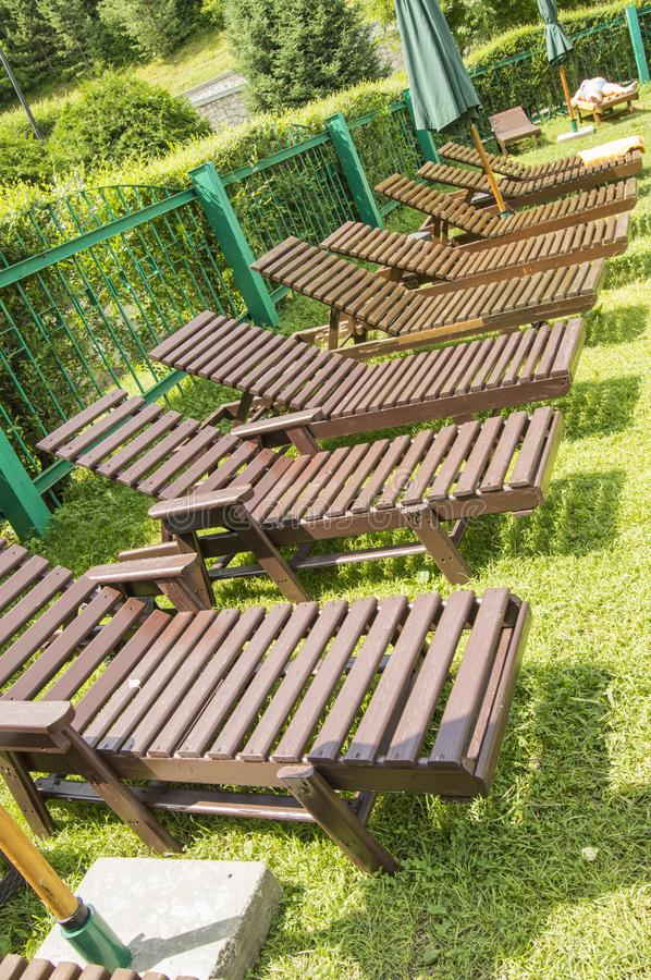 Wooden deck chairs line the green grass under the sun in the relaxation area of the modern luxury hotel. Garden for. Wooden deck chairs stand in a row on the royalty free stock photos