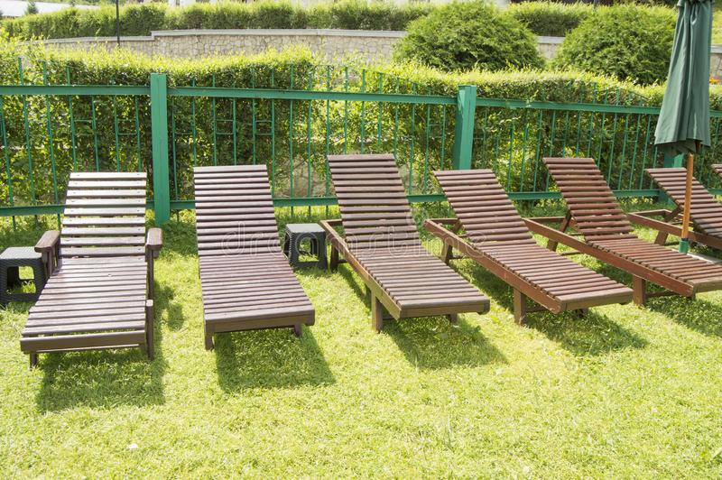 Wooden deck chairs stand in a row on the green grass under the sun in the recreation area on the private territory of a. Modern luxury hotel. Garden for stock photo