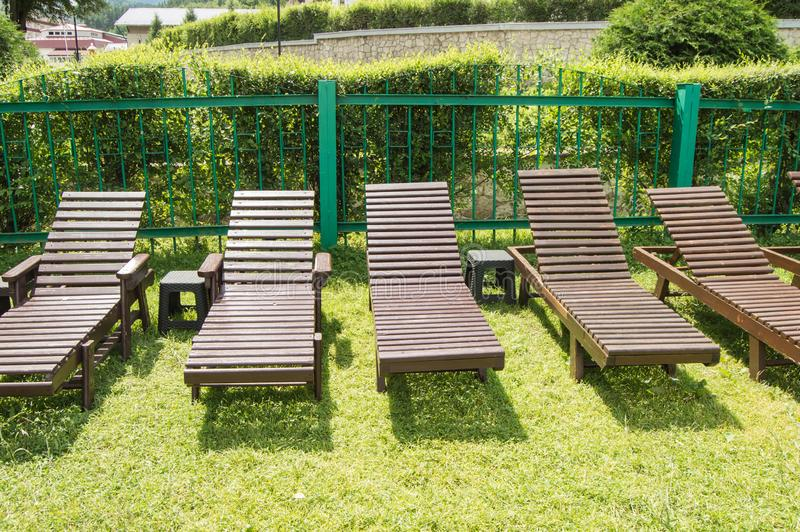 Wooden deck chairs stand in a row on the green grass under the sun in the recreation area on the private territory of a modern. Luxury hotel. Garden for stock photo