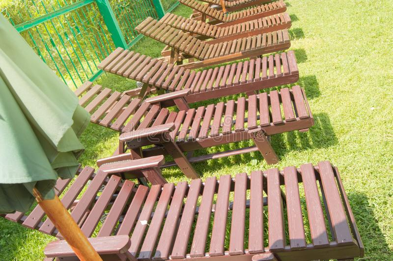 Wooden deck chairs stand in a row on the green grass under the sun in the recreation area on the private territory of a modern. Wooden deck chairs stand in  row stock photography