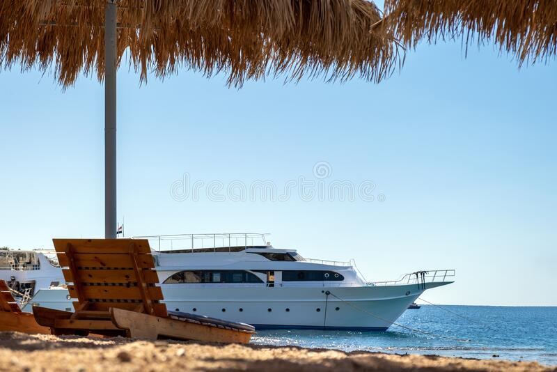 Wooden deck chairs under rough straw sun umbrella on sea beach and big white yacht ship in water near shore on sunny summer day.  stock photography